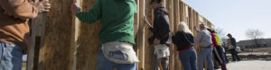 Several volunteers work together to build a structure with Habitat for Humanity.