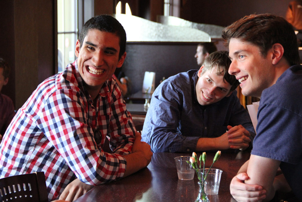 Three members of the Fellows program are smiling and sitting together in a restaurant.