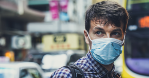 man standing on a sidewalk wearing a surgical face mask