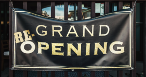 sign announcing business's grand re-opening