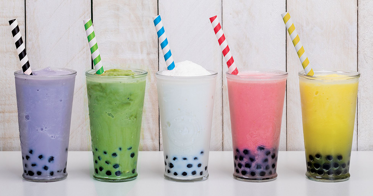 row of five drinking glasses holding colorful drinks and paper straws