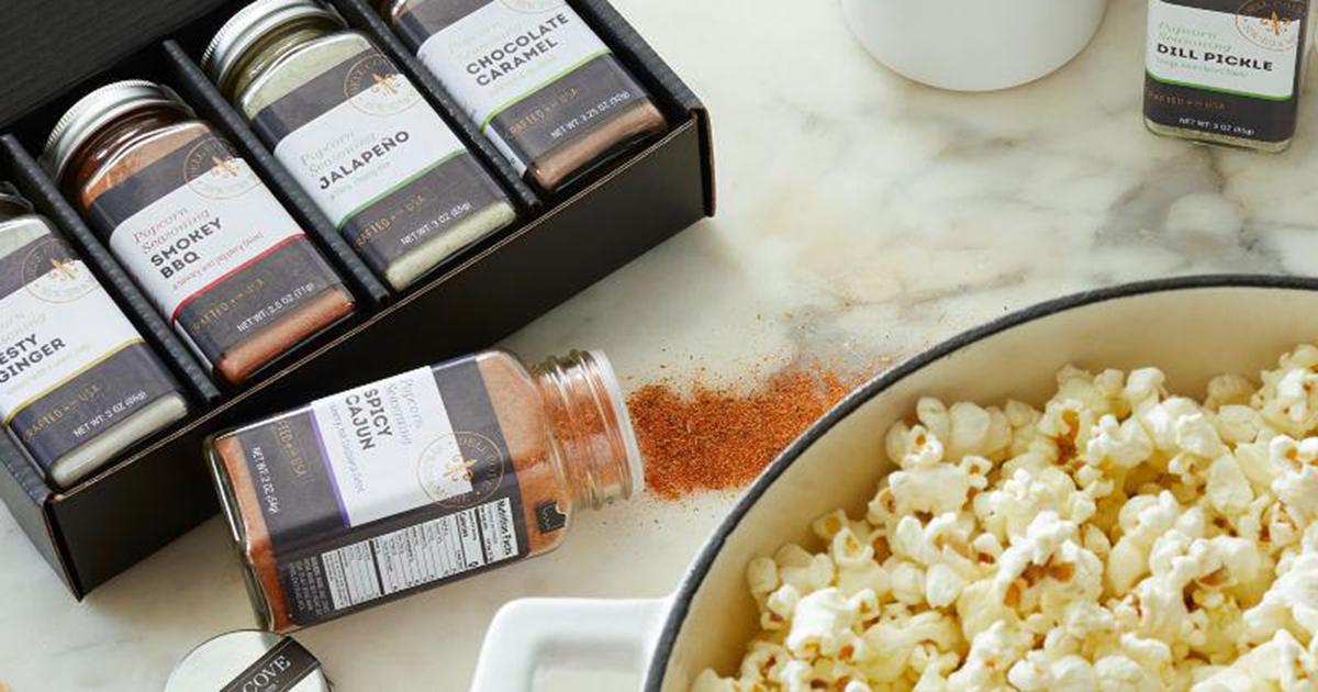 popcorn seasonings in glass containers, next to a bowl full of popcorn kernels