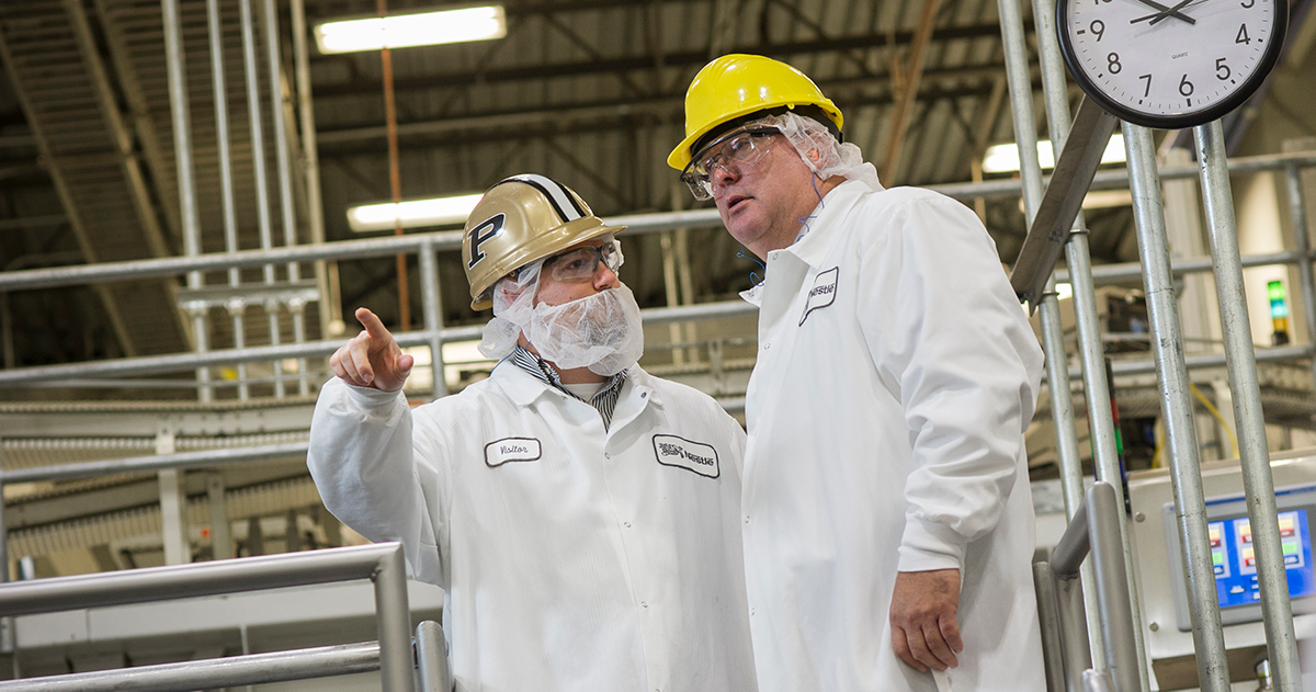 two people talking on a factory floor
