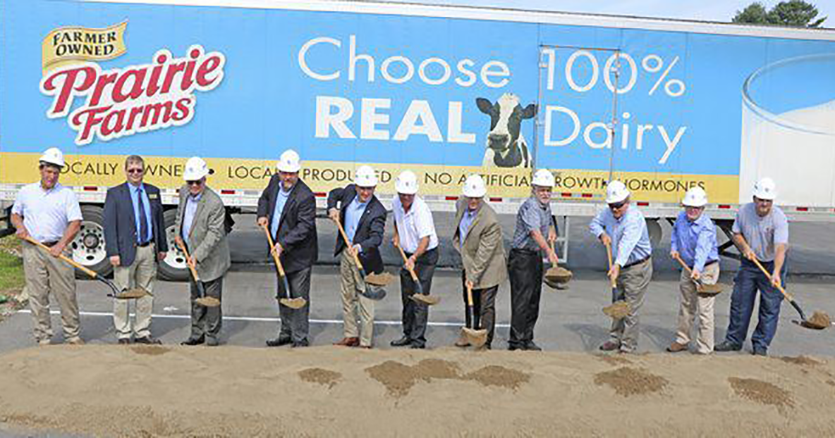people wearing hard hats participating in a groundbreaking ceremony