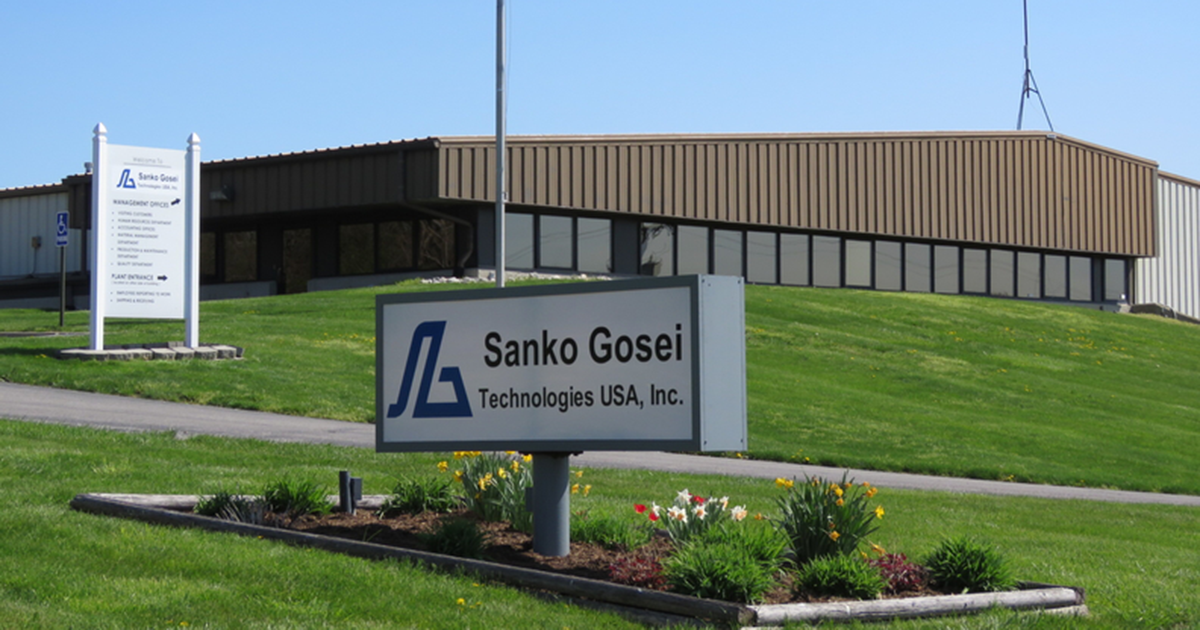 exterior photo of an industrial building with a sign in the foreground